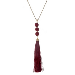 "Gold tone necklace with a burgundy fabric tassel and three thread wrapped beads. Approximately 30"" in length."