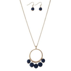 "Gold tone necklace set with an open circle pendant, navy blue thread wrapped wrapped bead fringe, and matching fishhook earrings. Approximately 32"" in length."