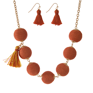"""Gold tone necklace set with orange thread wrapped beads, tassel accents and matching fishhook earrings. Approximately 16"""" in length."""