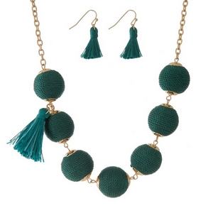 "Gold tone necklace set with emerald green thread wrapped beads, tassel accents and matching fishhook earrings. Approximately 16"" in length."