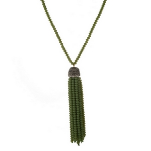 "Green beaded necklace with a monochromatic tassel pendant. Approximately 30"" in length."