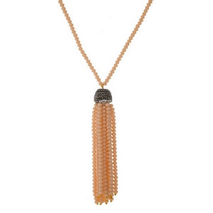 "Peach beaded necklace with a monochromatic tassel pendant. Approximately 30"" in length."