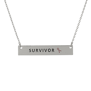 "Dainty silver tone, Breast Cancer Awareness necklace with a bar pendant, stamped with ""Survivor."" Approximately 16"" in length."