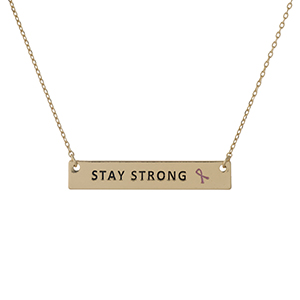 "Dainty gold tone, Breast Cancer Awareness necklace with a bar pendant, stamped with ""Stay Strong."" Approximately 16"" in length."