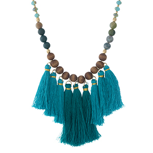 "Turquoise and wooden beaded, gold tone necklace with teal and turquoise tassels. Approximately 24"" in length."