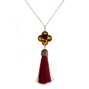 "Gold tone necklace with a tortoise shell clover pendant and a thread tassel. Approximately 30"" in length."