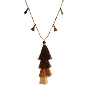 "Shades of brown beaded necklace with a brown ombre, tiered tassel pendant. Approximately 30"" in length."