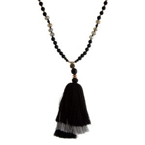 "Gold tone necklace with natural stone beads and a two tone, tiered tassel pendant. Approximately 32"" in length."