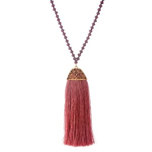 "Faceted bead necklace with gold tone accents and a thread tassel. Approximately 32"" in length."