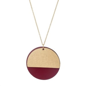 "Gold tone necklace with a leather circle pendant and a metal half circle pendant. Approximately 32"" in length."