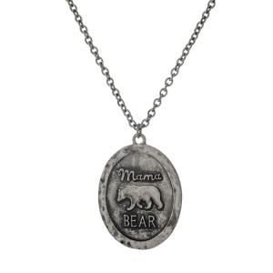 "Burnished metal necklace with a hammered circle pendant stamped with ""Mama Bear."" Approximately 16"" in length."