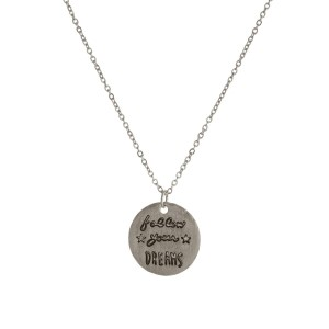 "Dainty metal necklace with a circle pendant, stamped with ""Follow Your Dreams."" Approximately 16"" in length. Necklace comes with a pouch, perfect for gifting!"