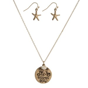 """Dainty, metal necklace set with a circle pendant stamped with """"all you need is vitamin sea"""" and matching fishhook earrings. Approximately 16"""" in length."""