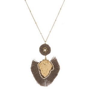 "Gold tone necklace with a hammered, bohemian pendant and fanned, thread tassels. Approximately 32"" in length."