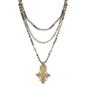 """Three layer, natural stone beaded necklace with a burnished gold tone, cross pendant. Approximately 18"""" to 24"""" in length. Handmade in the USA."""
