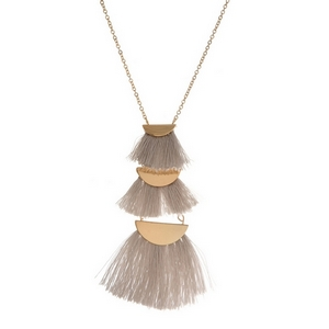 "Dainty gold tone necklace with a tiered three tassel pendant. Approximately 18"" in length."