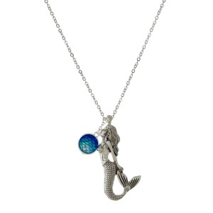 """Long, silver tone necklace with a mermaid pendant and a rhinestone pendant. Approximately 32"""" in length."""