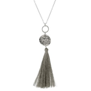 """Long, metal necklace with a coin pendant and metallic thread tassel. Approximately 30"""" in length."""