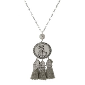 """Long, metal necklace with a coin pendant and three metallic thread tassels. Approximately 30"""" in length."""