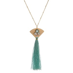 """Gold tone necklace with a rhinestone pendant and a thread tassel. Approximately 33"""" in length."""