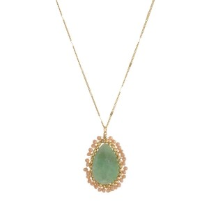 """Gold tone necklace with a natural stone pendant, wrapped with faceted beads. Approximately 32"""" in length."""