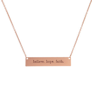 "Dainty metal necklace with a bar pendant stamped with message, ""believe. hope. faith."" Approximately 16"" in length."