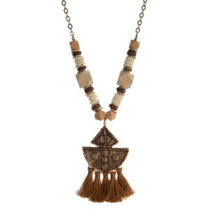 "Long necklace with wooden beads and boho pendant accents with soft tassels. Approximately 32"" in length."