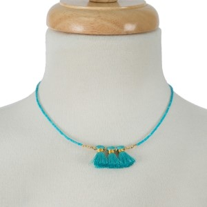 "Dainty, short necklace with three soft tassels. Approximately 16"" in length."