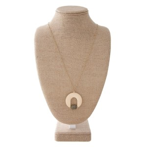 """Long gold tone necklace with metal pendant accent with natural stone. Approximately 32"""" in length with a 2"""" pendant."""