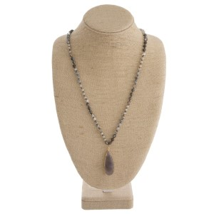 "Long beaded necklace with natural stone oval pendant. Approximately 32"" in length with a 2"" pendant."