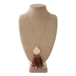 "Long gold tone necklace with metal pendant with faux leather detail. Approximately 32"" in length with a 4"" pendant."