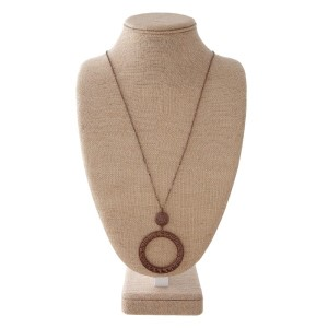 """Long metal necklace with boho cutout pendant. Approximately 32"""" in length with a 2.5"""" pendant."""