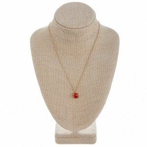 """Long metal necklace with a ruby-inspired natural stone pendant. Pendant approximately 1cm in diameter.  Approximate 21"""" in length."""