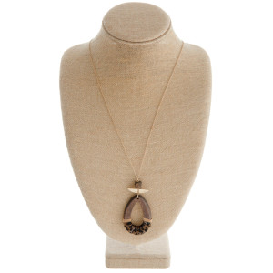 "Long gold chain necklace featuring a teardrop pendant with faux leather detail and gold accents. Pendant approximately 3"". Approximately 42"" in length."