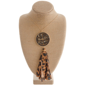 """Long gold chain necklace featuring a circular pendant with wood detailing and a fabric cheetah print tassel. Approximately 36"""" in length. From pendant to end of tassel is approximately 9""""."""