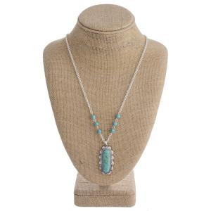 """Long necklace featuring a turquoise natural stone pendant with metal details and beaded accents. Pendant approximately 1.5"""". Approximately 32"""" in length overall."""