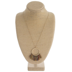 "Long dainty chain necklace featuring a circular pendant with thread fan tassel details. Pendant approximately 3"". Approximately 36"" in length overall."