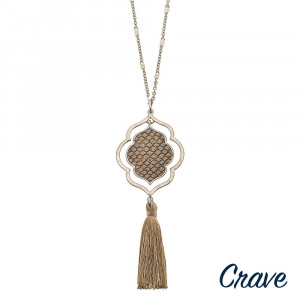 """Long gold chain necklace featuring a lotus pendant with faux leather snakeskin details and a tassel accent. Pendant approximately 4.5"""". Approximately 36"""" in length overall."""