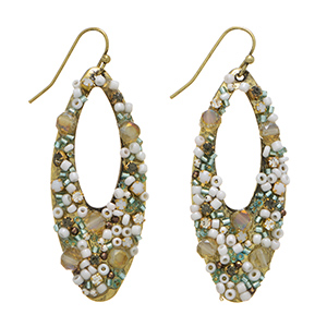 "Burnished gold tone fishhook earrings featuring a cutout oval shape with ivory and mint green seed bead decor. Approximately 1 7/8"" in length."