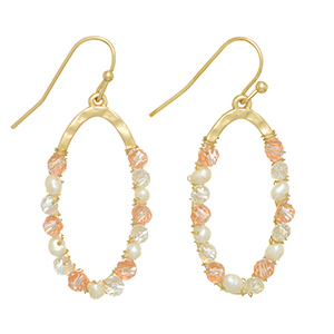 "Gold tone fishhook earrings featuring an oval with wire wrapped peach and clear beads and faux pearls. Approximately 1 1/4"" in length."