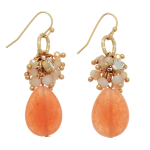 "Gold tone fishhook earrings featuring a cluster of beige glass beads with a peach teardrop shaped natural stone. Approximately 1 3/8"" in length."