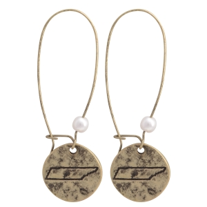"Burnished gold tone fishhook earrings featuring a disk stamped with the state of Tennessee and a faux pearl accent. Approximately 1 1/2"" in length."