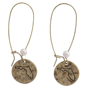 """Burnished gold tone fishhook earrings featuring a disk stamped with the state of Florida and a faux pearl accent. Approximately 1 1/2"""" in length."""