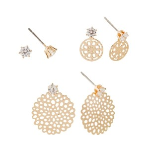Gold tone set of three post style earrings with a rhinestone stud, a stud with a hanging flower, and a stud with a hanging pom pom.