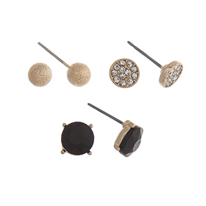 Gold tone set of three post style earrings displaying a textured ball, a pave disk, and a black stud.