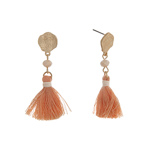"Matte gold tone drop earrings displaying a cream bead with a linked peach tassel. Approximately 2"" in length."