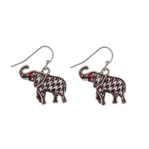"Silver tone fishhook earrings with a houndstooth elephant and red rhinestones. Approximately 1"" in length."