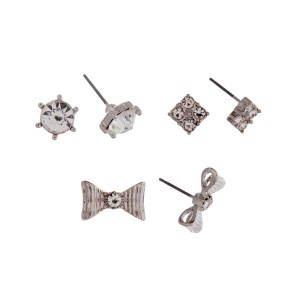 Silver tone set of three post style earrings displaying a pave square stud, clear rhinestone stud and a silver tone bow stud.