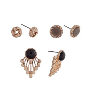 Gold tone three pair earring set with knot studs, black stone studs and black studs with metal fringe.