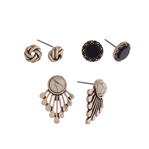 Burnished gold tone three pair earring set with knot studs, black stone studs and ivory studs.